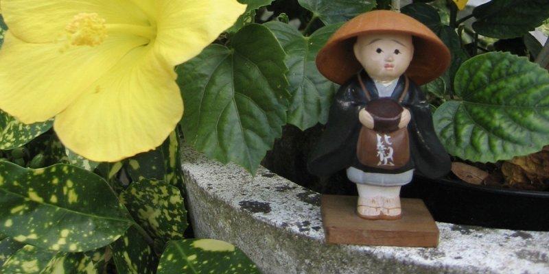 Monk and flower at zen temple de La Gendronnière